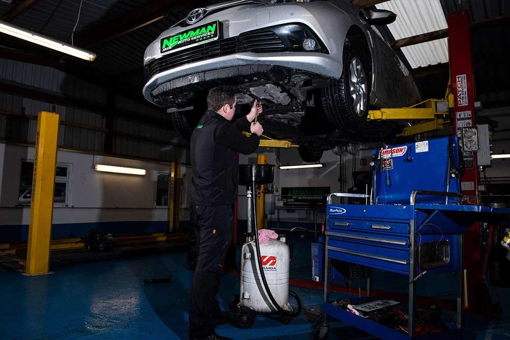 mechanic fixing underbelly of car