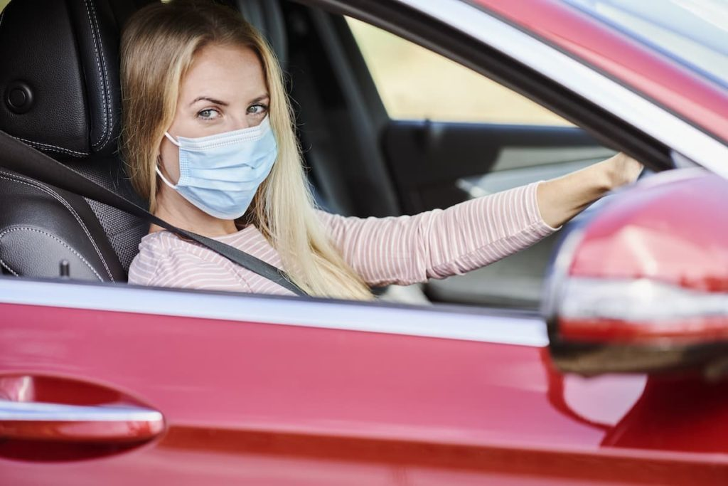 Safe driving, safe living. Woman in car with a facemask